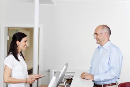 amigas conversando: Paciente var�n feliz y recepcionista mirando el uno al otro