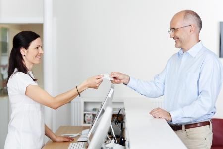 Medio volwassen vrouwelijke receptioniste ontvangen kaart van patiënt in tandarts kliniek