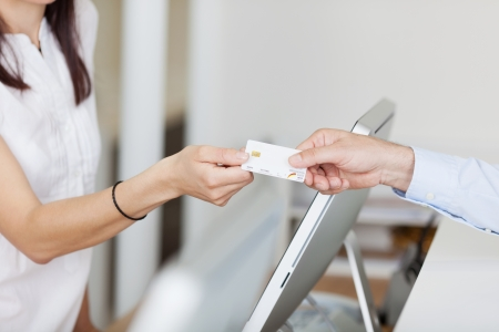 recepcionista: Primer plano de recepcionista recibir la tarjeta de paciente masculino en la clínica dentista