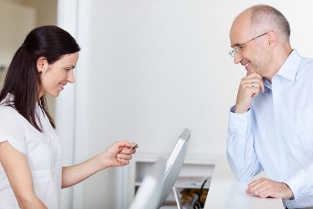 pagando: Vista lateral de mediados recepcionista mujer adulta en busca de tarjetas de ID de paciente en la cl�nica dentista Foto de archivo