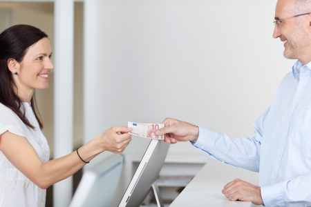 pay bill: Side view of mid adult female receptionist receiving 10 euro from patient in dentist clinic Stock Photo