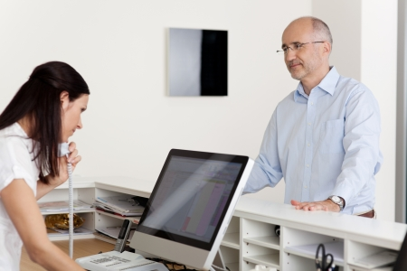 Mature male patient looking at female receptionist using landline phone and computer at reception in dentists clinic Stock Photo