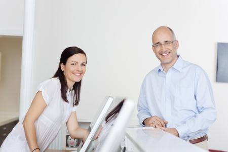 幸せな男性患者と歯科医の診療所でフロントの受付係の肖像画
