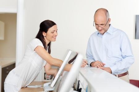recep��o: Retrato de paciente do sexo masculino e recepcionista na recep