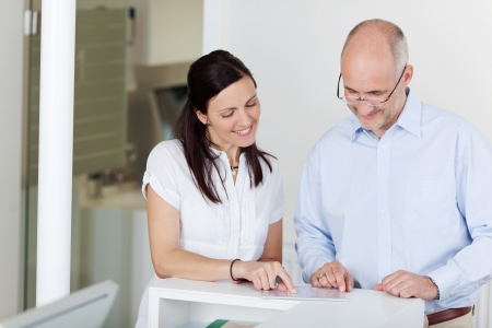 Portrait of male patient and receptionist looking at document at counter
