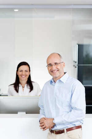 Portrait of happy mid adult patient and receptionist at reception in dentists clinic Stock Photo