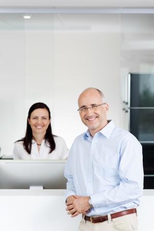 Portret van gelukkig medio volwassen patiënt en de receptioniste bij de receptie in de kliniek tandarts