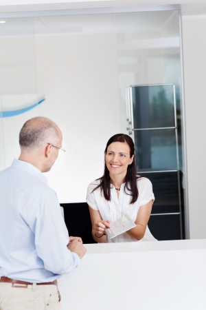 Portrait of female receptionist explaining form to patient in dentist clinic photo