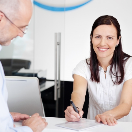 secretaries: Portrait of female receptionist explaining form to patient in dentist clinic Stock Photo