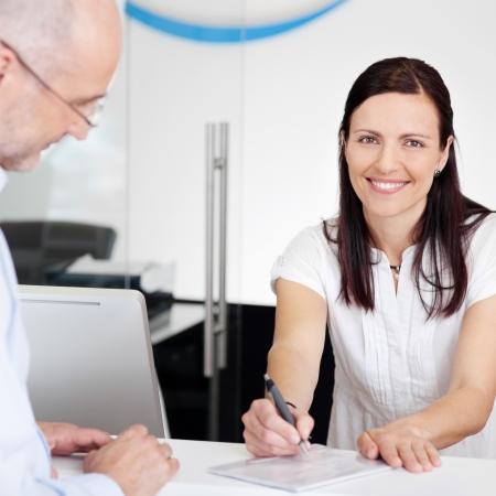 Portret van vrouwelijke receptioniste uitleggen formulier naar de patiënt in tandarts kliniek