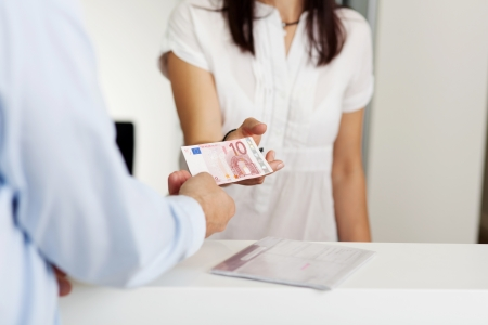 pay desk: Cropped image of patient paying money to receptionist in dentist clinic
