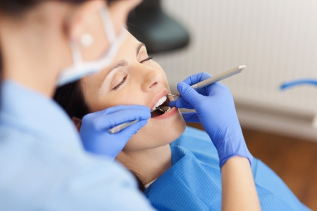 dentist mask: Closeup of female dentist examining mid adult patients mouth in clinic Stock Photo