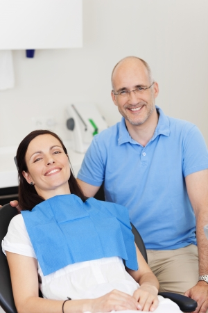 Portrait of dentist and patient smiling in clinic