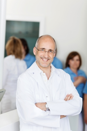 Portrait of male mid adult dentist smiling with assistants in background at clinic photo