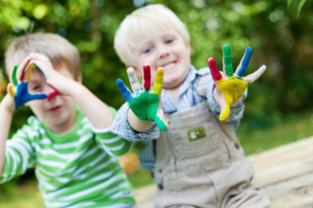 kids painted hands: Happy children showing their colorful painted hands