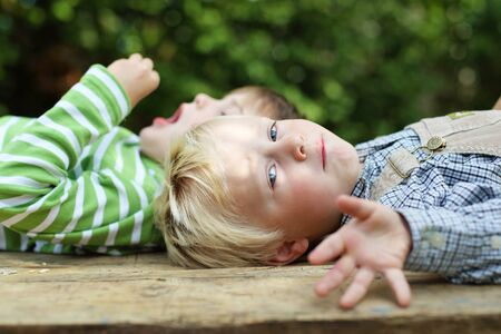 outstretching: Two boys lying in the garden over the blurred nature background Stock Photo