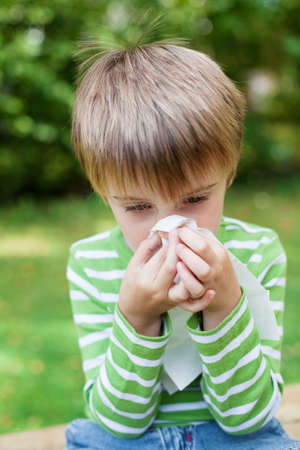 Little boy blowing his nose because of allergy in the garden Stock Photo - 21259726