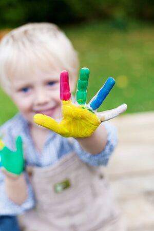 Creative playful child showing his colorful painted hands photo