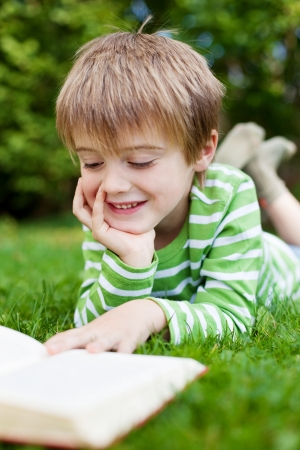 Happy little boy reading book on the grass in garden photo