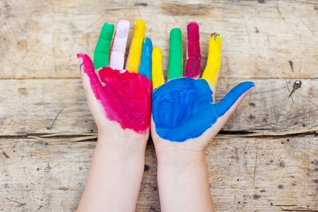 Colorful painted hands over the wooden background photo