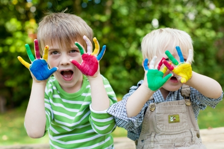 Two children showing their colorful painted hands