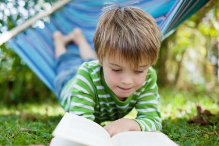 Vrolijke jongen lezen boek liggend op de hangmat