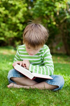 crossed legs: Cute young boy sitting on the grass and reading book Stock Photo