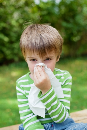Little boy covering his nose because of allergy photo