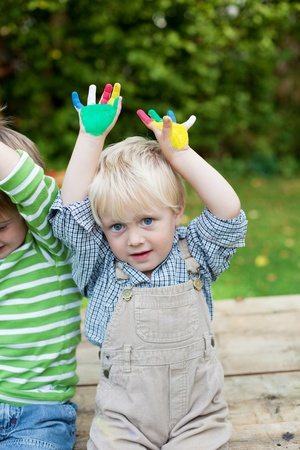 Two little boys having fun with their colorful painted hands photo