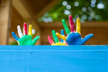 fingerpaint: Little children showing their colorful hands inside the playhouse