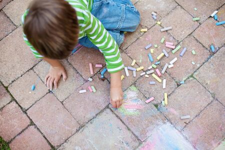 ground floor: Young little boy drawing on the pavement using colorful chalk