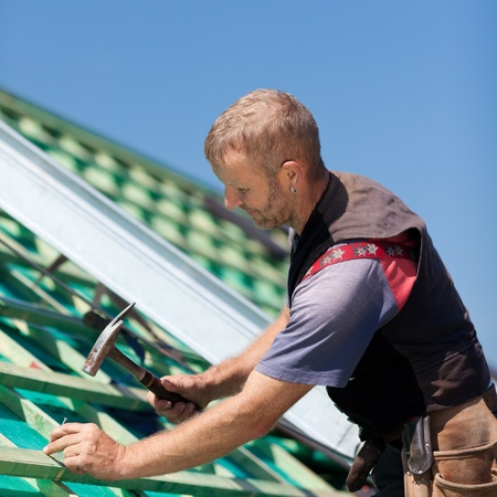 waterproofing: Roofer hammering nails into roof beams for the construction of the roof Stock Photo