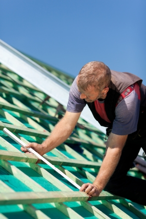 waterproofing: Roofer measuring the roof beams distance on a sunny day