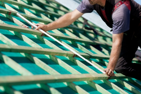roof framework: Close-up of a roofer measuring the roof beams distance on a sunny day Stock Photo