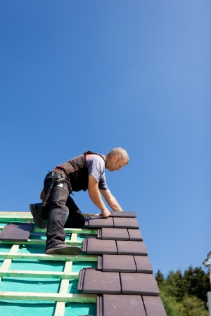 ridgeline: Roofer assembling gray tiles over the beams on a sunny day