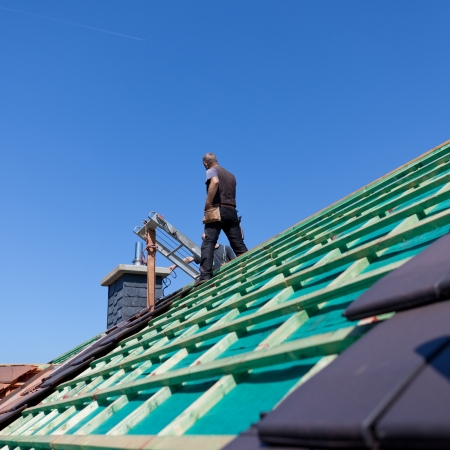 Detail of the construction of a new roof with the roofer standing on the background Stock Photo - 21259855