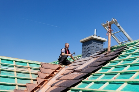 Roofer hammering nails on the beams on top of an unfinished roof Stock Photo - 21259856