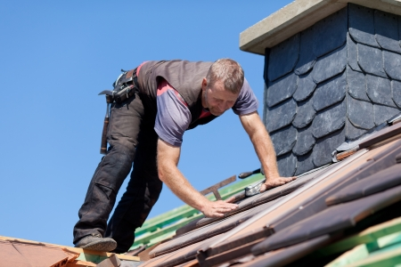 タイルを確認する煙突の横にある屋根葺き職人 写真素材