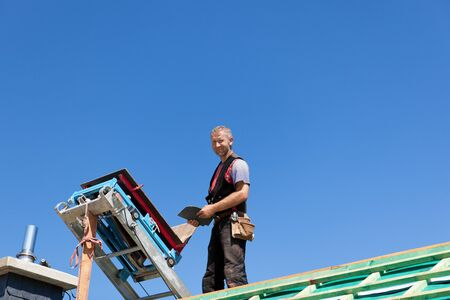 Roofer standing near a construction elevator on top of an unfinished roof on a sunny day photo