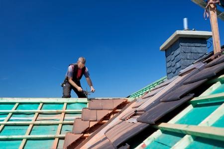workingman: Primer plano de las vigas de un techo sin terminar con el techador trabajando en segundo plano