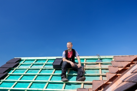 Roofer resting on top of a new unfinished roof Stock Photo - 21259864