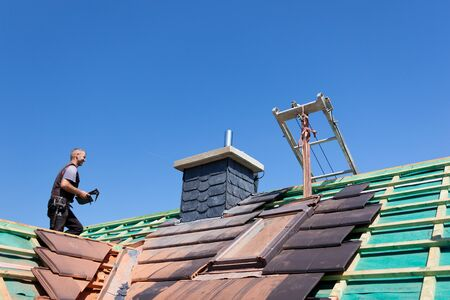 workingman: Roofer carrying gray tiles across the roof