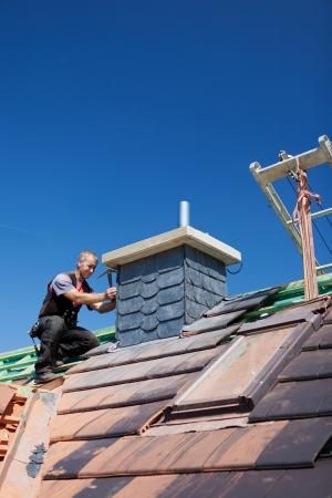 workingman: Roofer montaje azulejos en una chimenea de un techo sin terminar Foto de archivo