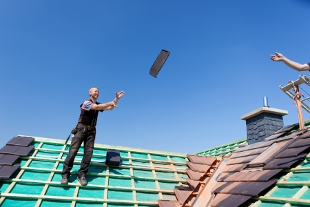 Two roofers transfer tiles across the roof by tossing them through the air Stockfoto