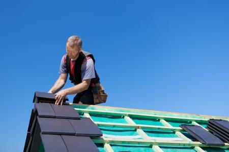 Dakdekker assembleren randen tegels naar de top van de onvoltooide dak Stockfoto