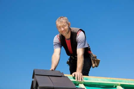 roof ridge: Portrait of a smiling roofer on top of the roof Stock Photo