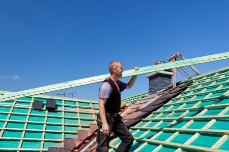 Dakdekker klimmen het dak met een dakbalk in de richting van het verzamelpunt Stockfoto