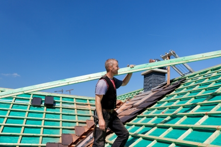 assembly point: Roofer climbing the roof with a roof beam in direction of the assembly point
