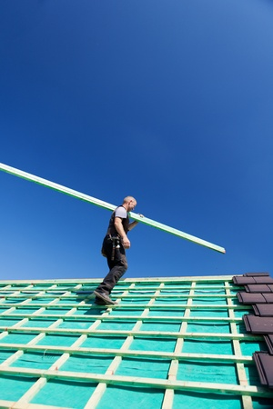 assembly point: Low angle view of a roofer climbing the roof with a beam in direction of the assembly point