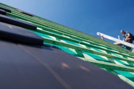 Close-up detail van grijze leisteen tegels op een onvoltooide dak met houten balken op de achtergrond